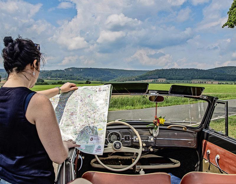 Frau im Cabrio liest Landkarte, Blick aufs Weserbergland