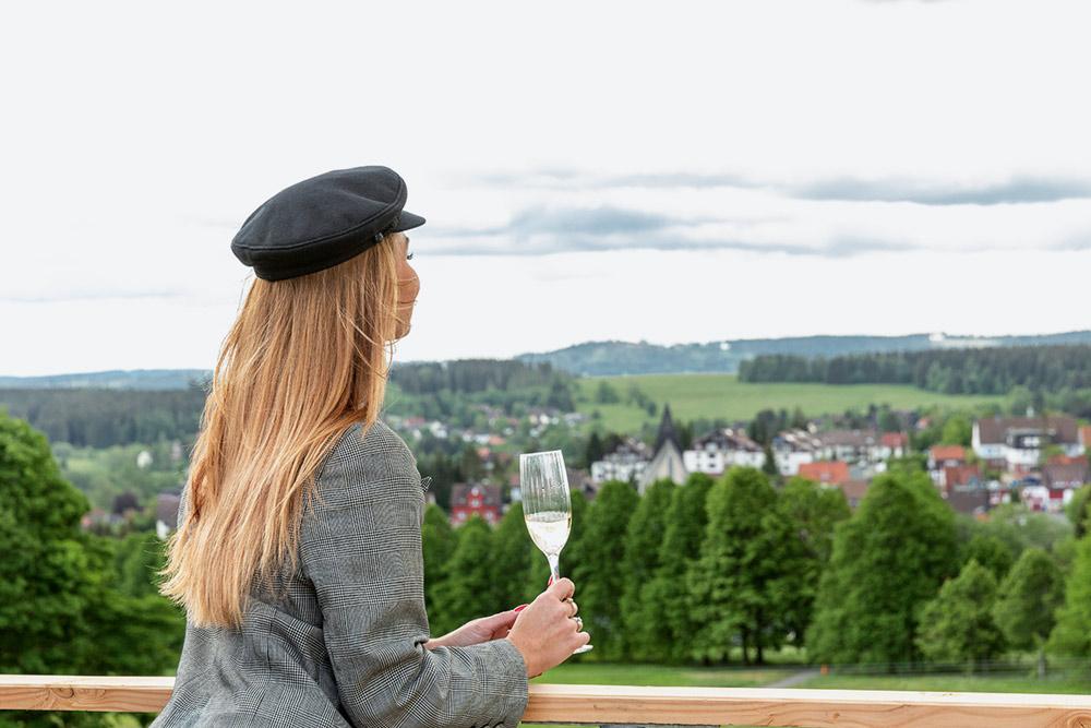 Frau trinkt Sekt mit Blick auf den Harz
