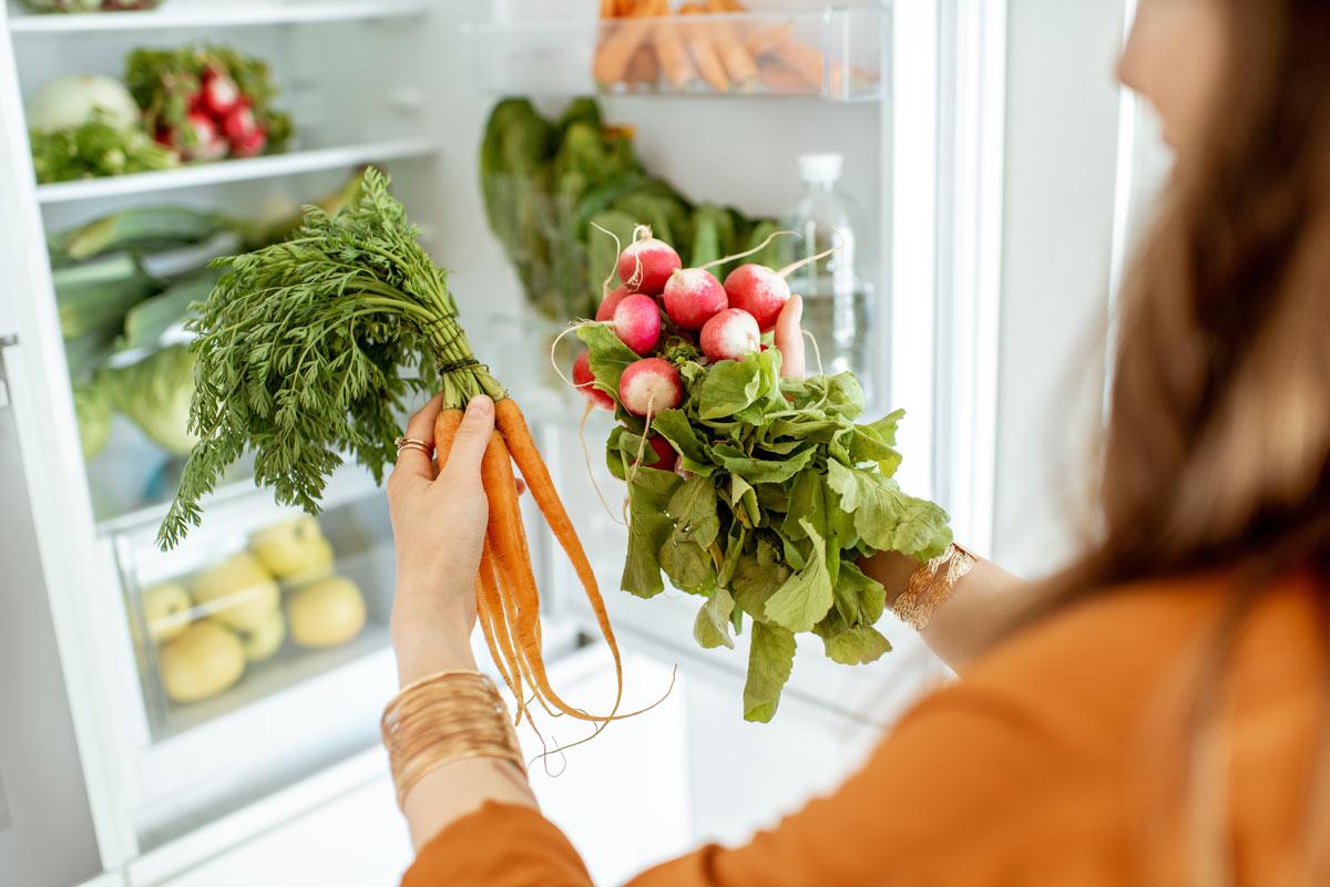 Frau nimmt Karotten und Radieschen aus dem Kühlschrank